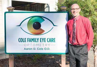 Aaron D. Cole O.D. standing next to a Cole Family Eye Care sign.